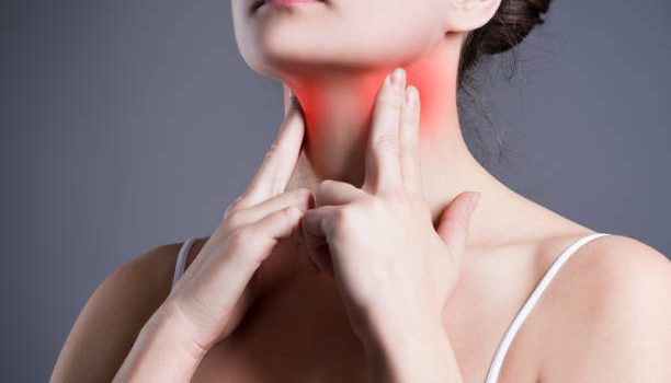 Sore throat, woman with pain in neck, gray background, studio shot